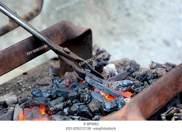 Blacksmithing, heating of the metal horseshoes on coals