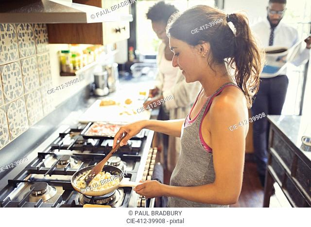 Young woman cooking scrambled eggs on stove in kitchen
