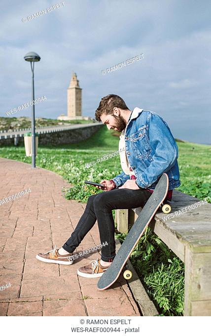 Spain, A Coruna, young man with longboard using smartphone