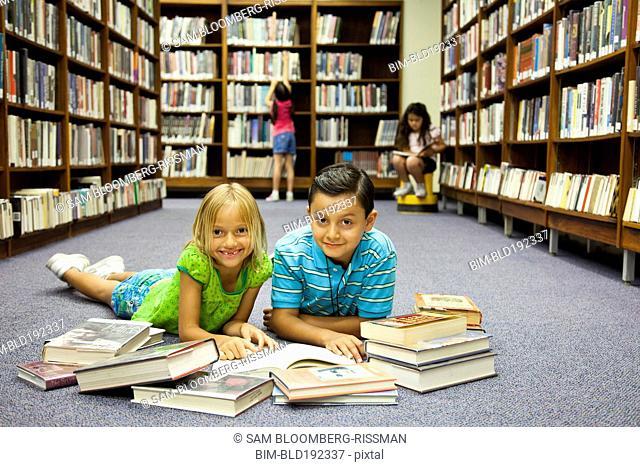 Children reading books on library floor