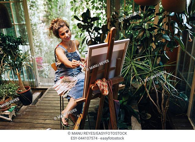 Indoor shot of professional smiling female artist painting on canvas in studio with plants
