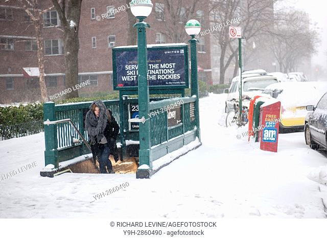 Pedestrians exit the subway in the Chelsea neighborhood of New York. Originally predicted as a blizzard with up to 20 inches of snow the storm has changed its...