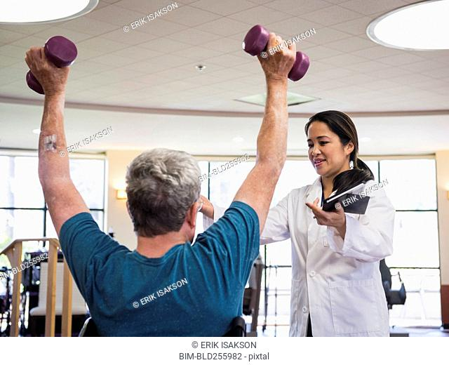 Physical therapist helping man lifting weights