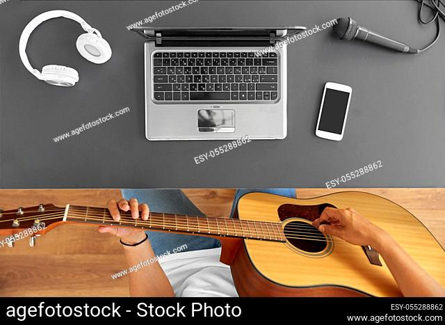 young man with laptop playing guitar at table