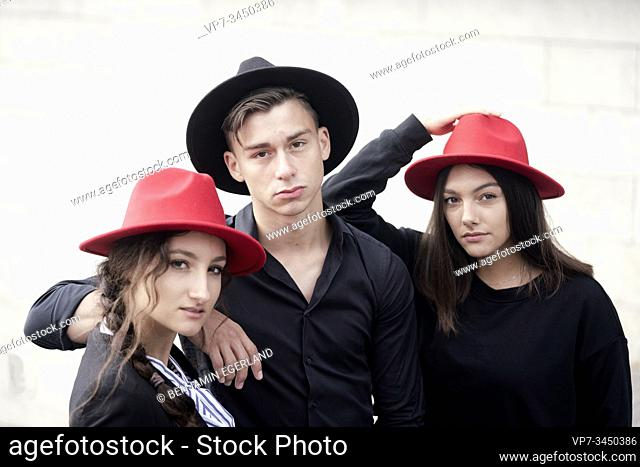 Man and two women wearing hats. Munich, Germany