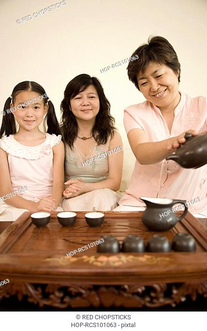 Mature woman pouring tea into a teapot with another mature woman and her daughter sitting beside her
