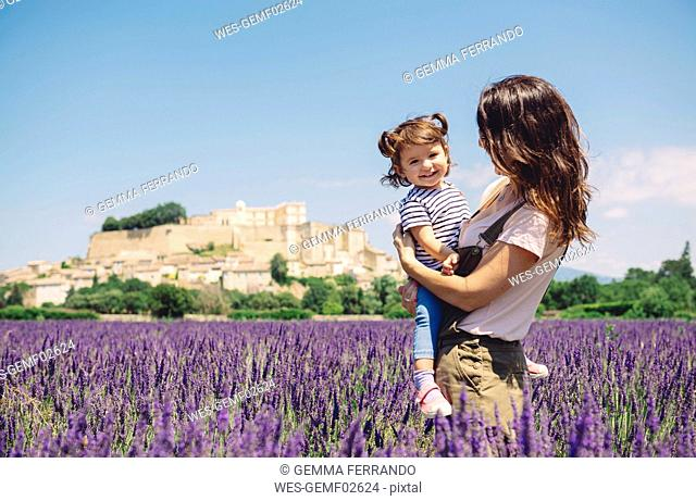 France, Grignan, portrait of happy baby girl together with her mother in lavender field
