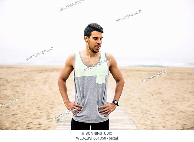 Portrait of athlete with earbuds on the beach