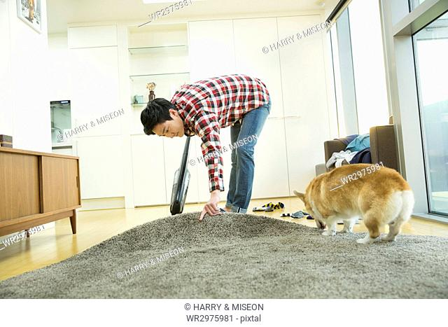 Young bachelor with a pet dog cleaning his house