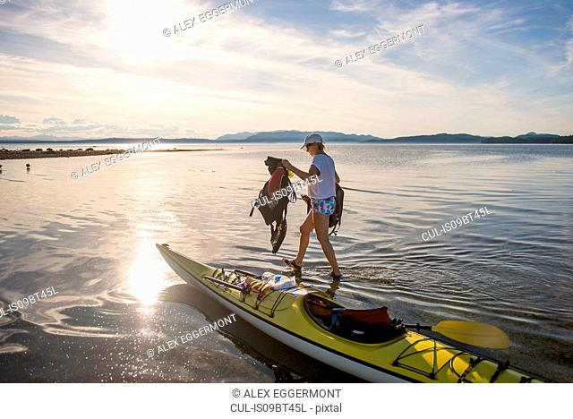 Mature female kayaker carrying life jackets from kayak, Quadra Island, Campbell River, Canada