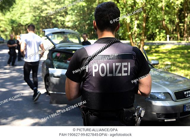 27 June 2019, Mecklenburg-Western Pomerania, Lärz: During a vehicle check, festival visitors are checked by police officers on a parking lot on their way to the...