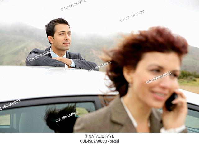 Businessman leaning on car, woman on cell phone
