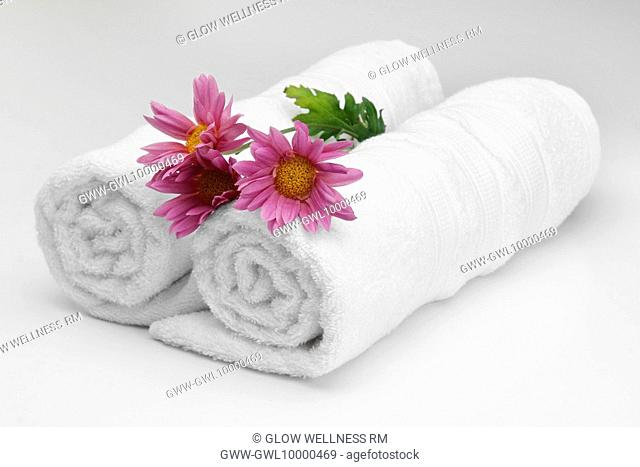 Close-up of rolled up towels with flowers