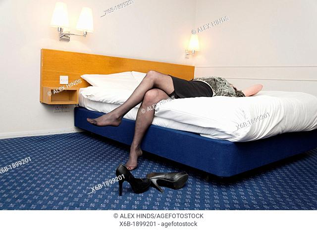 Older woman lying back on bed in hotel room