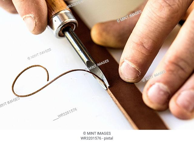 High angle close up of craftsman making brown leather camera strap, using a forked cutter, an edging tool on the leather