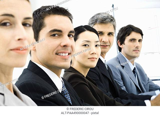 Row of business executives in conference room, smilng at camera