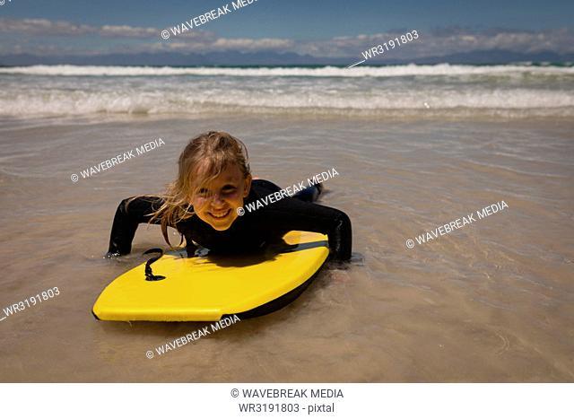 Happy girl surfing at beach