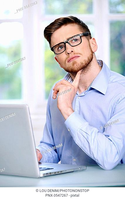 man in a blue shirt, glasses, beard, serious, window out of focus in the background, sitting, in front of a computer laptop; looking up, finger under the chin