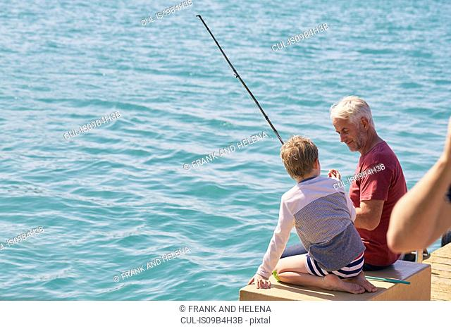 Grandfather and grandson fishing on houseboat sun deck, Kraalbaai, South Africa