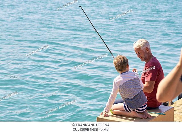 Grandfather and grandson fishing on houseboat sun deck, Kraalbaai, South Africa