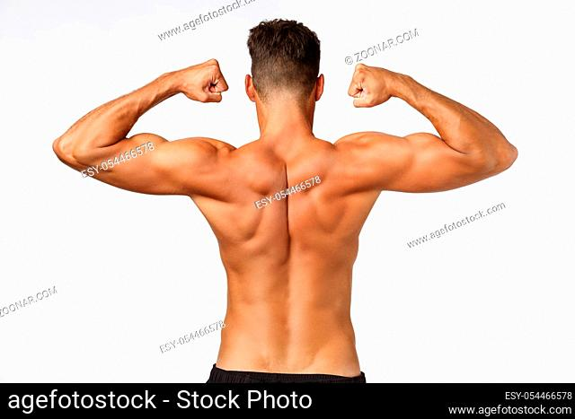 Rear view shirtless musclar man back, raising hands and tighten muscles, showing perfect body shape, workout and bodybuilding concept