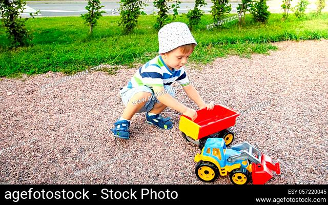 Portrait of cute 3 years old toddler boy sitting on playground at park and playing with colorful plastic toy truck. Child having fun and playing outdoors with...