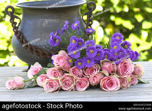 Purple aster and pink roses with a antique vase