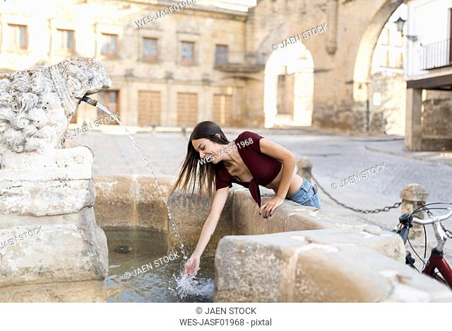 Spain, Baeza, laughing young woman splashing with water of a fountain