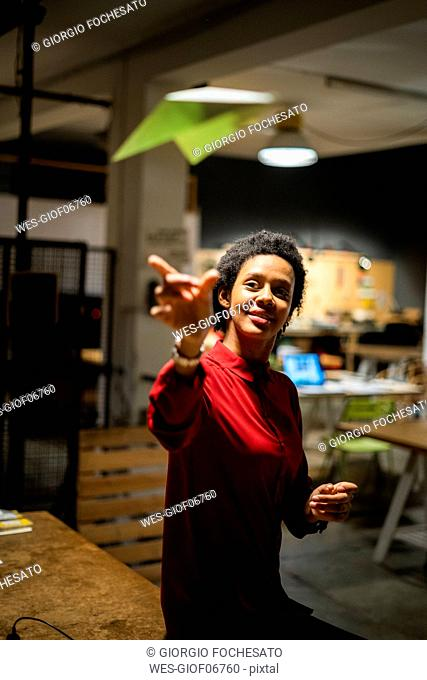 Businesswoman throwing a paper plane in office