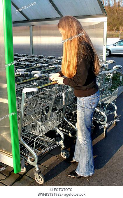 young woman with shopping cart on a parking lot