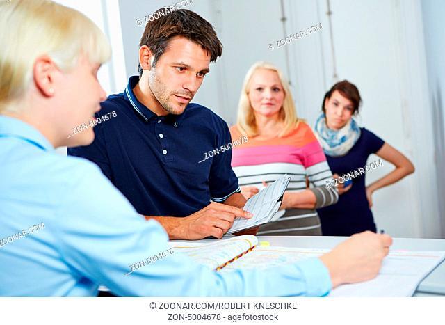Mann beim Arzt mit Terminkalender vereinbart einen Termin mit der Sprechstundenhilfe