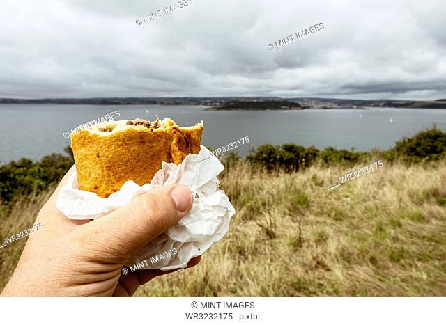 A hand holding a half eaten Cornish pasty