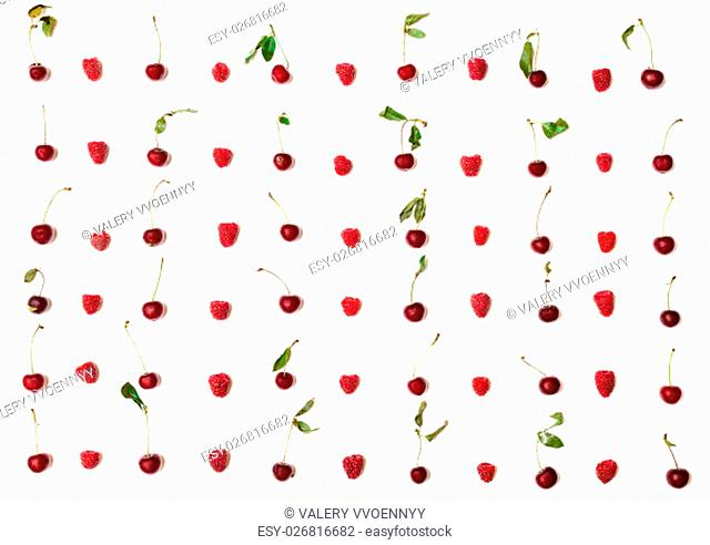 lot of raspberries and cherries arranged on white background