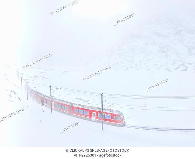 Bernina Express train at Bernina Pass during a snowstorm, canton of Graubünden, Engadin Valley, Switzerland