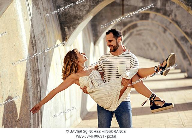 Spain, Andalusia, Malaga, happy man carrying girlfriend under an archway in the city