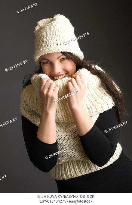 Beautiful adult woman wearing knitted wear, gray background