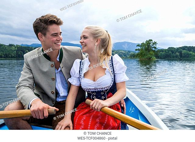 Germany, Bavaria, happy young couple wearing traditional clothes sitting in a rowing boat on Staffelsee