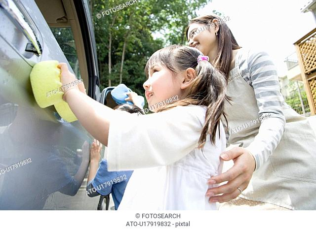 Boy and Girl Washing Car With Mother