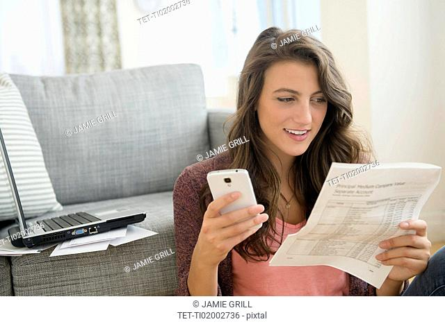 Woman in living room with papers and smartphone
