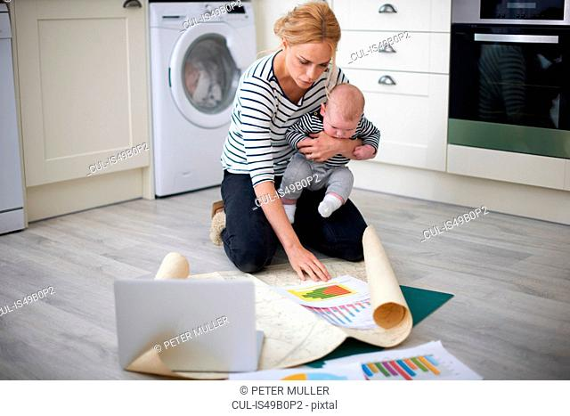 Woman holding baby son in arms, while looking through graphs on kitchen floor
