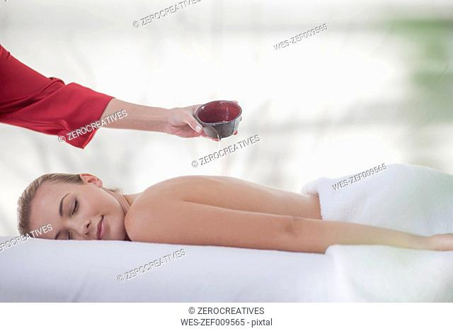 Oil is being poured over young woman lying on massage table at spa