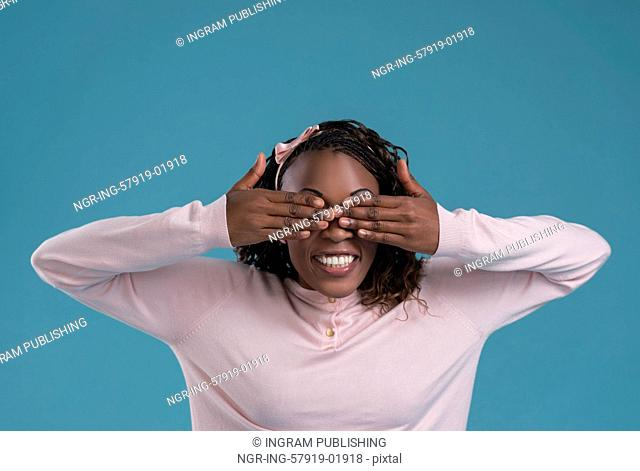 Portrait of cute african woman posing - hiding eyes with hands