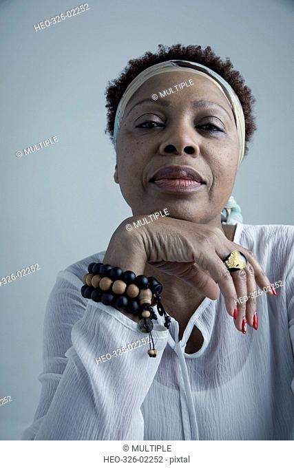 Portrait confident African American mature woman wearing headscarf and beaded bracelet