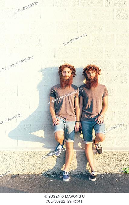 Portrait of identical adult male twins with red hair and beards against white wall