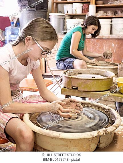 Students shaping pottery on wheels in ceramic studio