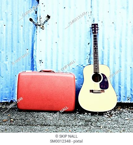 A guitar and old suitcase sit in front of an old shed