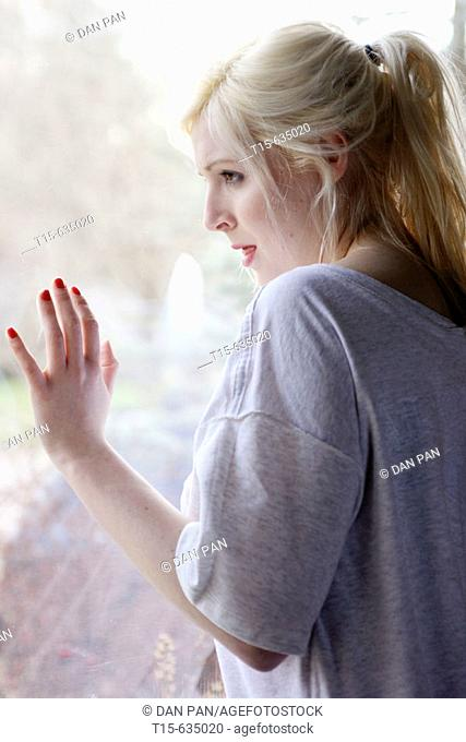 Young woman looking out of window, sad, depressed, anticipating something, boredom