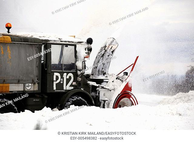 Highspraying snowblower at work. Scandinavia