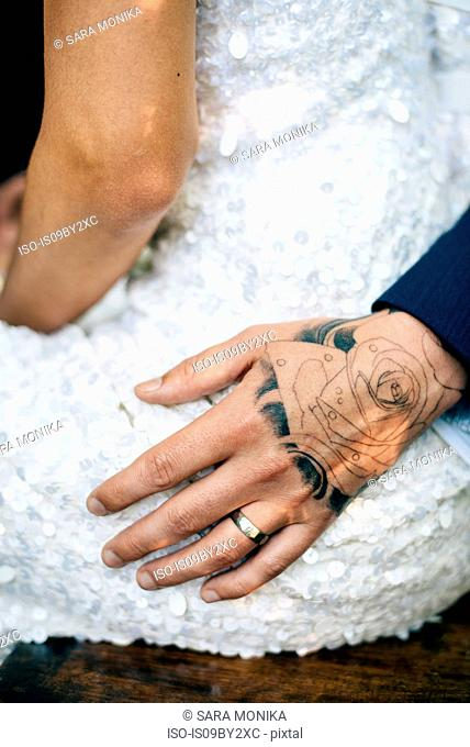 Groom's tattooed hand on bride's hip, mid section