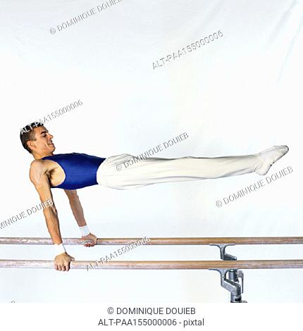Young male gymnast performing routine on parallel bars, side view